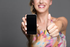 Woman with mobile giving a thumbs up of approval. Woman with a modern smartphone giving a thumbs up of approval and endorsement as she holds the blank screen royalty free stock images