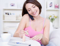Woman with mobile making manicure Stock Image