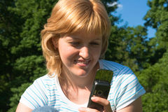 Woman with a mobile phone. The beautiful woman dials number on a mobile phone Royalty Free Stock Photos
