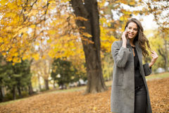 Woman with mobile phone in the autumn park Royalty Free Stock Images