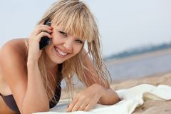 Woman with mobile phone on beach Royalty Free Stock Images
