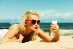 Woman with mobile phone on beach Stock Image