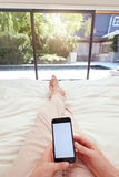 Woman with mobile phone on bed Stock Image