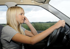 Woman with mobile phone in the car Royalty Free Stock Images