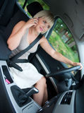 Woman with mobile phone in the car Stock Photography