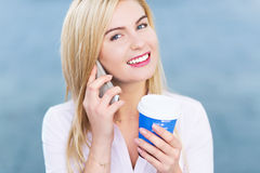 Woman with mobile phone and coffee to go Stock Photos
