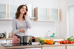 Woman With Mobile Phone While Cooking Stock Photos