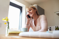 Woman On Mobile Phone In Modern Apartment Stock Photo