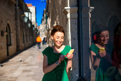 Woman with mobile phone in old city street Royalty Free Stock Photo