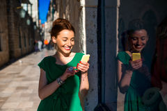 Woman with mobile phone in old city street Stock Photo