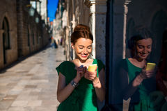 Woman with mobile phone in old city street Stock Photography