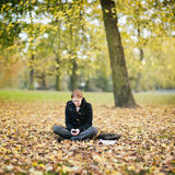 Woman with a Mobile Phone in a Park Stock Images