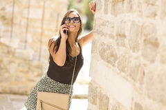 Woman with a mobile phone. Posing on the street Stock Photography