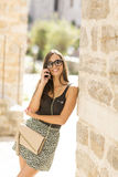 Woman with a mobile phone. Posing on the street Royalty Free Stock Photography