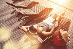Woman with mobile phone resting on deck chair and listening music. Intentional sun glare and lens flare effects Stock Image