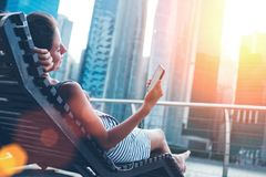 Woman with mobile phone resting on deck chair near skyscrapers. Intentional sun glare and lens flare effect Stock Image