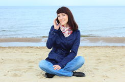 Woman with mobile phone sitting on the beach Stock Photo