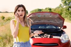 Woman with mobile phone standing near broken car in countryside stock photography