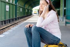Woman mobile phone station. Young woman talking on a mobile phone on railway station royalty free stock photography