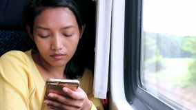 Woman with mobile phone in a train stock video