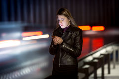 Woman with mobile phone walking at night next to highway royalty free stock photo