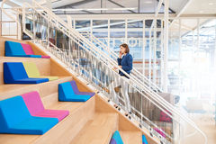 Woman on mobile phone walking up stairs in colourful office Royalty Free Stock Photos