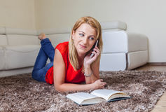 Woman on the Mobile while Reading a Book. Woman smiling on the mobile while reading a book lying on the floor in her room Stock Image