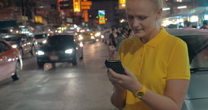 Woman with mobile at the roadside of night Bangkok, Thailand. Young Caucasian woman texting on smart phone standing by the road with intense car traffic in night stock footage