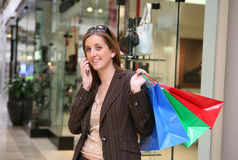 Woman with mobile shopping. Young woman with mobile telephone and colorful shopping bags, stores in background Royalty Free Stock Photos
