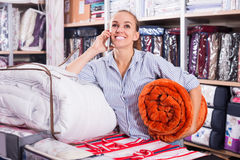 Woman with mobile shopping new blanket and coverlet Stock Photography