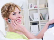 Woman with mobile speaking. Portrait of smiling beautiful cheerful woman with mobile speaking - indoors Royalty Free Stock Image