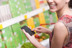 Woman with mobile at supermarket Royalty Free Stock Photography