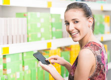 Woman with mobile at supermarket Stock Image