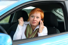 Woman with mobilein a car. Red-haired woman with mobile-phone in a car. She is thinking oups Royalty Free Stock Photo