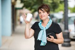 Woman With Mobilephone And Coffee Cup Waving. Portrait of beautiful young woman with mobilephone and disposable coffee cup waving Stock Photo