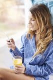 Woman with mobilephone. Young woman with orange juice and smartphone Stock Image