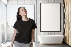 Woman before mockup poster in bathroom. Pondered woman in modern bathroom with mockup white poster on wooden wall royalty free stock photography