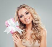 Woman modèle de sourire avec de longs cheveux sains avec le boîte-cadeau rose Photos libres de droits