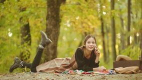 Woman model in autumn park with mobil phone. Happy woman hipster listen music on smart phone. Young female having fun. Over autumn background stock video footage