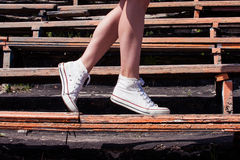 Woman model feet wearing sneakers walking down the bench of old Royalty Free Stock Images