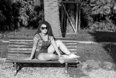 Girl sitting on a bench (sun). Model grayscale with light eyes Royalty Free Stock Photos
