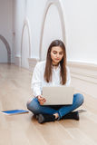 Woman model with long dark hair in white shirt and blue jeans sitting on floor in hall at college university working on laptop Royalty Free Stock Photo