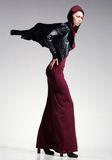 Woman model posing very dramatic in an minimal studio setup. Woman model in long dress and leather jacket posing very dramatic in an minimal studio setup Royalty Free Stock Photography