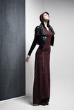 Woman model posing very dramatic in an minimal studio setup. Woman model in long dress and leather jacket posing very dramatic in an minimal studio setup Royalty Free Stock Images