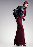 Woman model posing very dramatic in an minimal studio setup. Woman model in long dress and leather jacket posing very dramatic in an minimal studio setup Stock Images