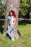 Woman with red hair in jean. Model posing in fashion style Royalty Free Stock Image