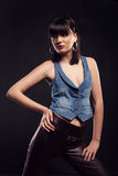Woman model posing in leather pants and jeans jacket in studio Stock Photos