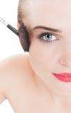 Woman model using make-up brush Royalty Free Stock Photo
