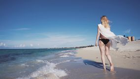 Woman model walking on the beach The beautiful blonde in a bikini walking on the beach. The beautiful blonde in a bikini and sunglasses walking on the beach. The stock video footage