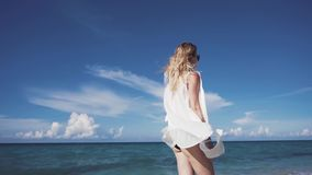 Woman model walking on the beach The beautiful blonde in a bikini walking on the beach. The beautiful blonde in a bikini and sunglasses walking on the beach. The stock footage